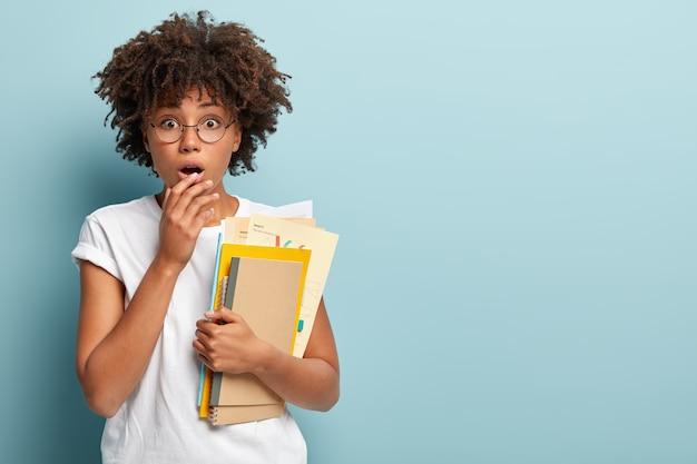 Foto van verbijsterde afro-amerikaanse student die extra cursussen gaat volgen, hijgt naar adem van verrassing, houdt de hand op de lippen Gratis Foto