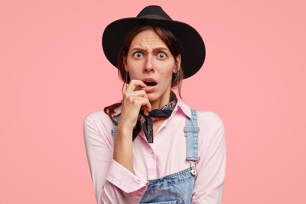 Foto van verbijsterde vrouw kijkt met verbijsterde uitdrukking, houdt vinger dichtbij geopende mond Gratis Foto