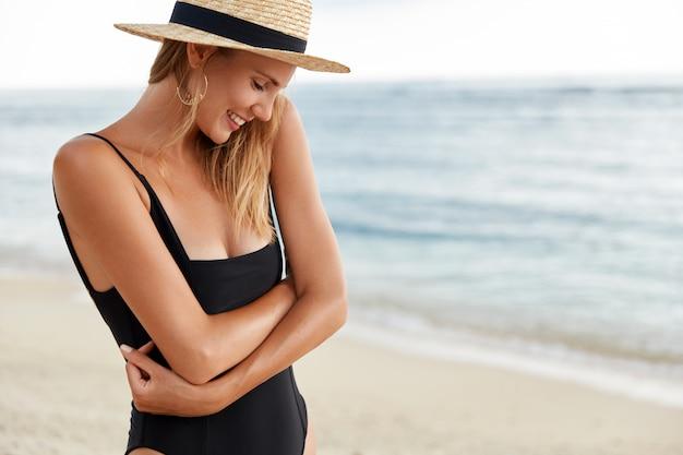 Foto van verlegen mooie vrouw houdt handen gekruist, draagt zwarte bikini en strooien hoed, poseert gelukkig over de blauwe oceaan, toont een gezonde, zuivere huid, blij om gefotografeerd te worden. mensen, vrije tijd, zomer Gratis Foto