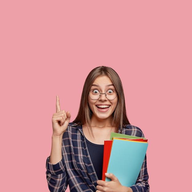 Foto van verrast europese vrouw wijst met wijsvinger naar boven, in goed humeur Gratis Foto