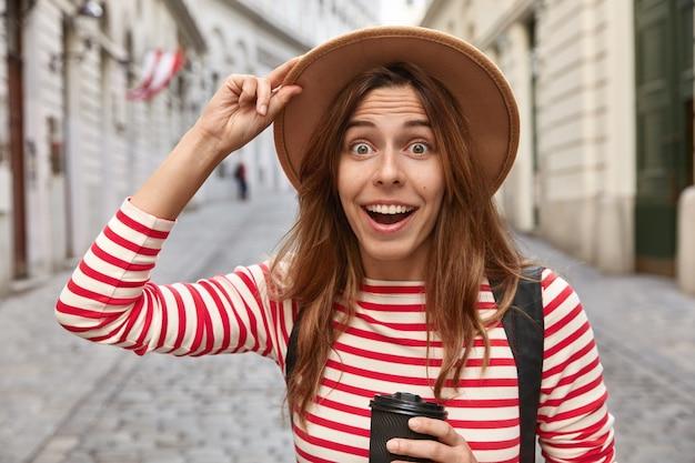 Foto van verrast vrolijke europese vrouw houdt hand op hoed, drinkt afhaalkoffie, wandelingen op straat Gratis Foto