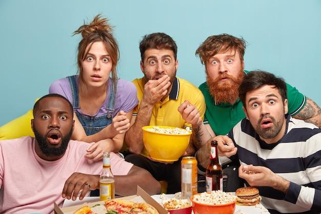 Foto van vijf vrouwen en mannen van gemengd ras kijken naar thrillerfilm, vreselijk nieuws, kijken in paniek, eten popcorn, staren met afgeluisterde ogen, geïsoleerd over blauwe muur, bang. enge film thuis Gratis Foto