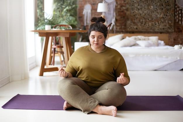 Foto van vreedzame kalme jonge mollige vrouw blootsvoets zittend op yoga mat thuis, mudra gebaar maken, mediteren met gesloten ogen. evenwicht, meditatie, harmonie, zen en wellness-concept Gratis Foto