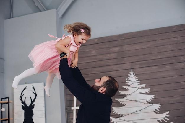 Foto van vrolijke blanke vader met kort dak haar verheugt zich en heeft veel plezier met zijn kleine schattige dochter in roze jurk in de nieuwjaarssfeer thuis Premium Foto