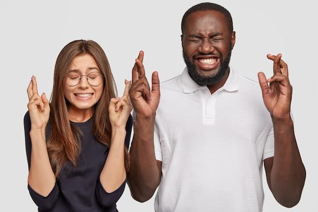 Foto van vrolijke donkere man, positieve europese vrouw kruis vingers Gratis Foto