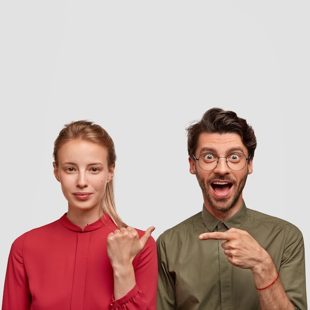 Foto van vrolijke hipster man met trendy kapsel, geeft met wijsvinger aan bij mooie dame in rode blouse. mooi stel wijst naar elkaar, staat dicht tegen witte muur met vrije ruimte erboven Gratis Foto