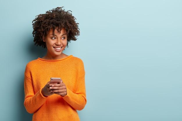 Foto van vrolijke opgetogen afro-amerikaanse vrouw typen sms op moderne mobiele telefoonapparaat, geniet van een goede internetverbinding Gratis Foto