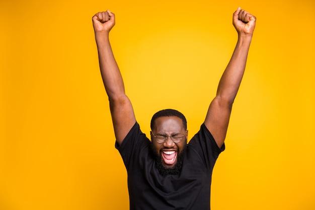 Foto van vrolijke positieve gekke opgewonden man in bril zwart t-shirt schreeuwen schreeuwen met onbeleefd gezicht expressie dromen handen omhoog geïsoleerde levendige kleuren muur Premium Foto