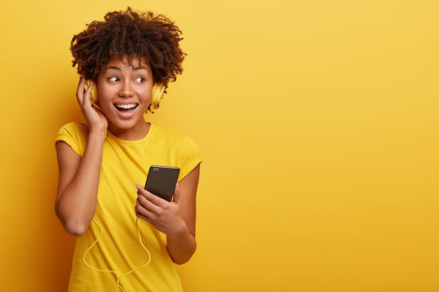 Foto van vrouwelijke meloman luistert favoriete afspeellijst in koptelefoon Gratis Foto