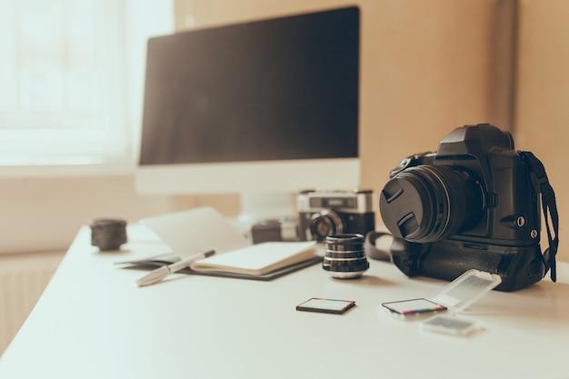 Foto van werkplek met camera en geheugenkaarten op voorgrond vervagen. moderne computer staat op witte tafel met notebook en pen naast liggen. Gratis Foto