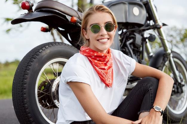 Foto van zorgeloze professionele jonge vrouwelijke motorrijder draagt trendy zonnebril en bandana, zit in de buurt van snelle zwarte motor, geniet van buiten rijden, zit op asfalt in de buurt van haar favoriete vervoer Gratis Foto