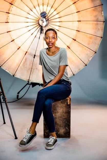 Fotograaf-assistent poseren voor een reflecterende paraplu in een studio Premium Foto