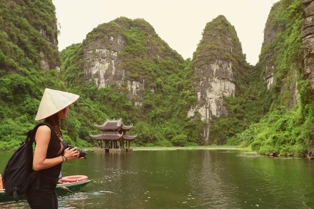 Fotograaf aziatische vrouw die slr camera professionele fotografie houden in ninh binh, vietnam Premium Foto