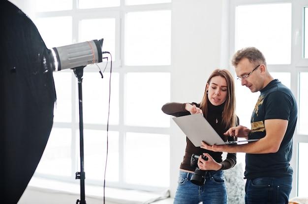 Fotograaf die over het schot uitlegt aan zijn assistent in de studio en kijkt op laptop. teamwerk en brainstorm. Premium Foto
