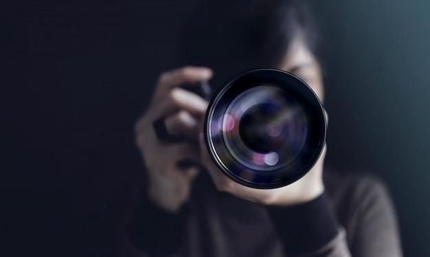 Fotograaf die zelfportret maakt. vrouw die camera gebruiken om foto te nemen. donkere toon, vooraanzicht. selectieve focus op lens. rechtstreeks in een camera Premium Foto