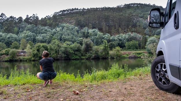 Fotograaf in een landschap met een macro-opname van de planten op de oever van de rivier Premium Foto