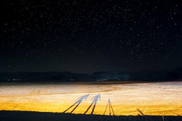 Fotografie met lange sluitertijd. een nightshot en de silhouetten van twee fotografen 's nachts in de winter Premium Foto