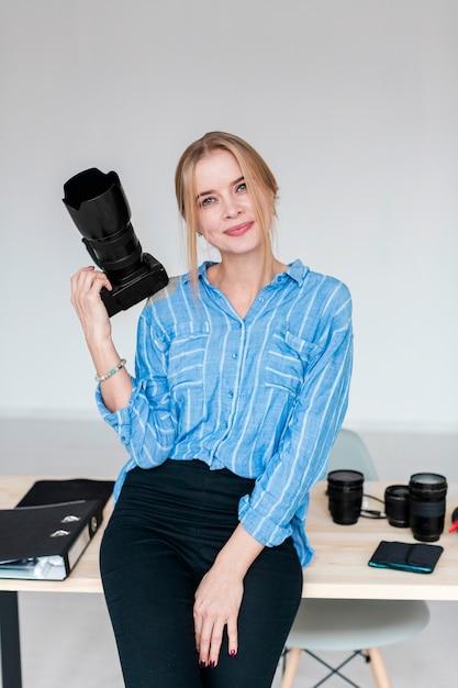 Fotografiestudio en vrouw die een camera houden Gratis Foto
