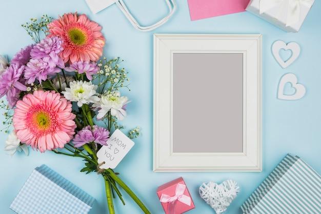 Fotokader dichtbij verse bloemen met titel op markering en decoratie Gratis Foto