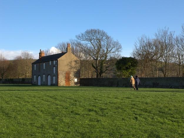 Fotoomheining twee mensen die op een omheind grasveld naar een oud gebouw lopen Gratis Foto