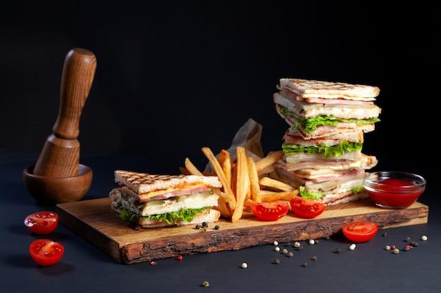 Fotosessie nieuw menu van koffiehuis, verse clubsandwich met kip en groenten, slasalade, friet en ketchup op hout Premium Foto