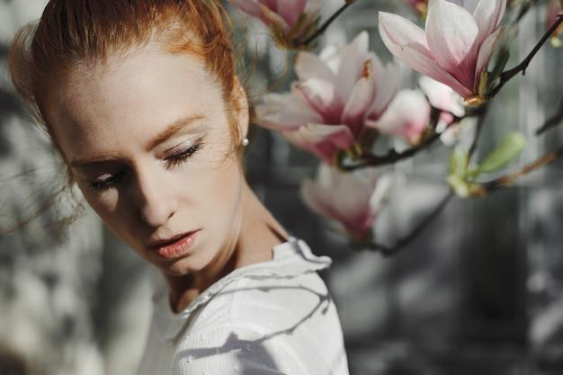 Fotoshoot van roodharige vrouw in de buurt van een magnolia bloemen Gratis Foto