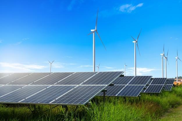 Fotovoltaïsche modules zonne-energiecentrale met windturbines op blauwe hemel Premium Foto