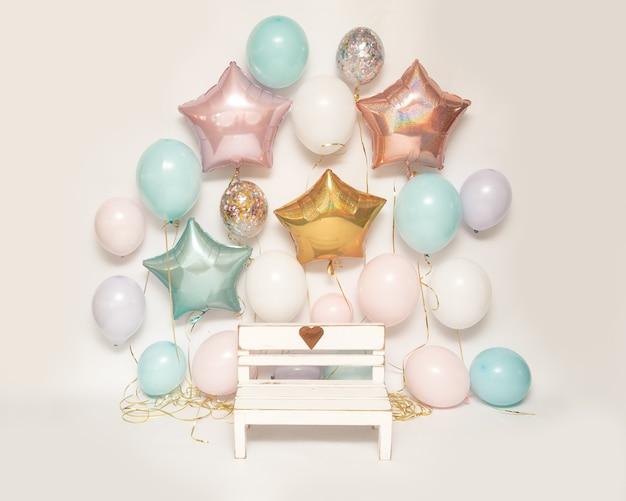 Fotozone op witte achtergrond met kleurrijke luchtgelballonnen en houten bankje met hart voor het maken van foto's van kinderen, verjaardagsdeel zone Premium Foto