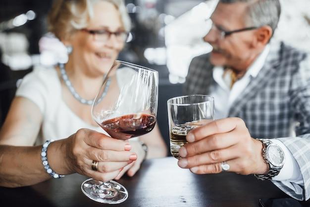 Fous bij de rode wijn in sumeer-terras. mooi stel, glazen, levensstijl. Premium Foto
