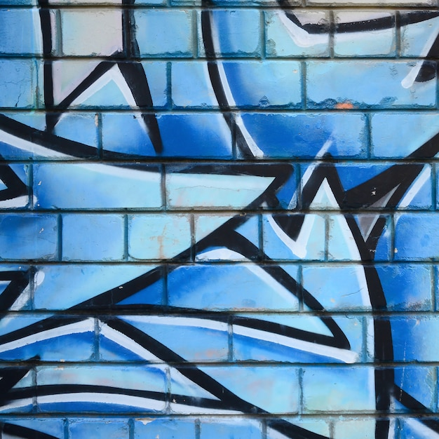 Fragment van graffititekeningen. de oude muur versierd met verfvlekken in de stijl van de straatkunstcultuur. gekleurde achtergrondstructuur Premium Foto