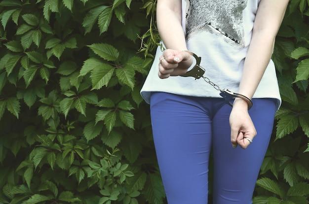 Fragment van het lichaam van een jonge misdadiger met handen in handboeien tegen een groene bloeiende klimop Premium Foto