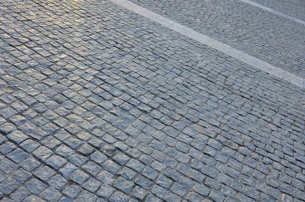 Fragment van het straatvierkant, gevouwen uit een grijze vierkante straatsteen Premium Foto