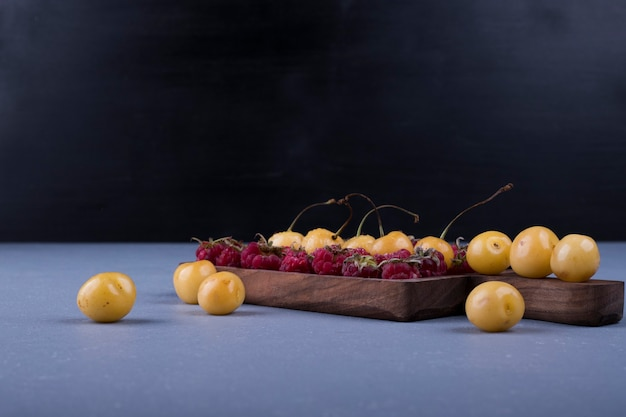 Frambozen en kersen in een houten schotel op donkere achtergrond Gratis Foto