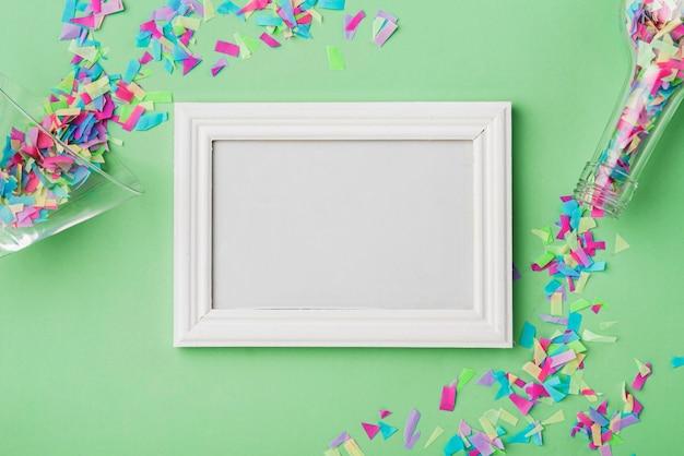 Frame en confetti met groene achtergrond Gratis Foto