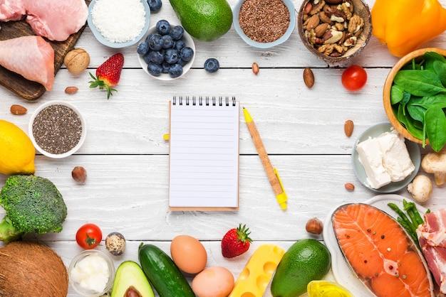 Frame gemaakt van keto ketogeen dieet van gezond voedselarme koolhydraten met papieren notitieblok. zeer goede vetproducten Premium Foto