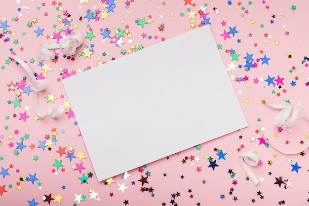 Frame met kleurrijke confetti sterren op roze achtergrond Gratis Foto