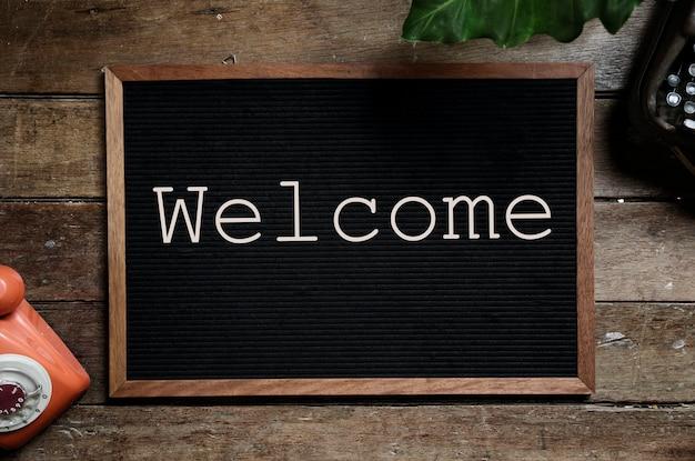 Frame met woord welkom op houten tafel Gratis Foto