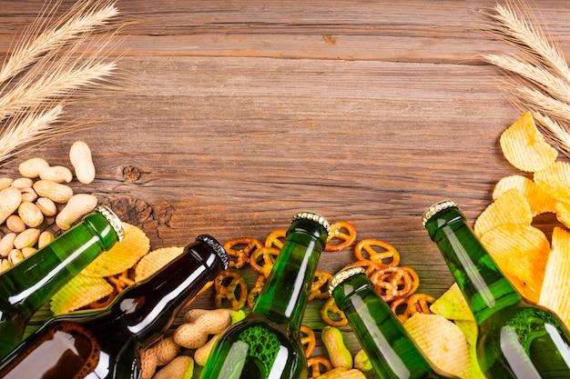 Frame van bier het groene flessen met pretzels Premium Foto