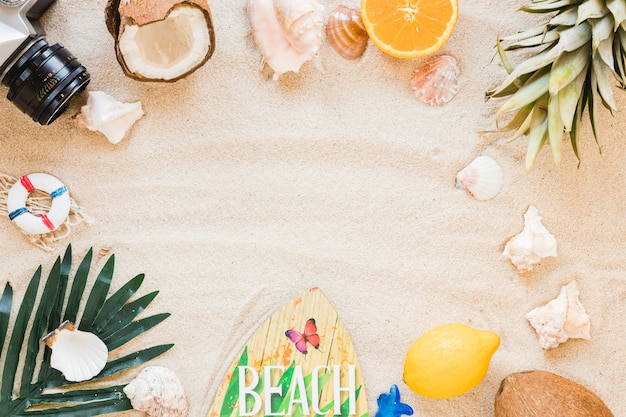 Frame van camera, exotisch fruit en surfplank op zand Gratis Foto