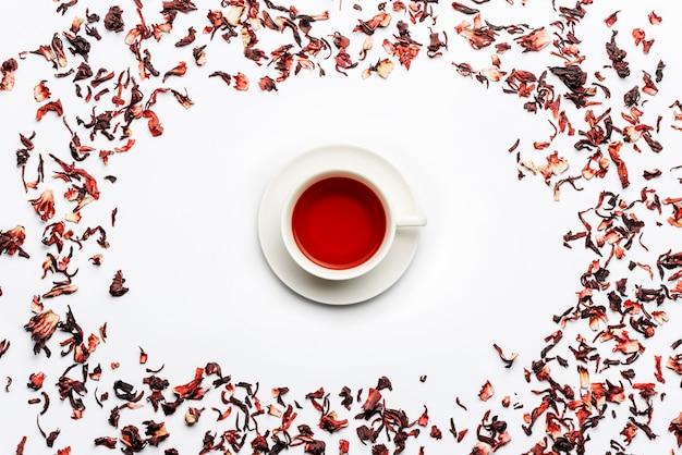 Frame van carcade theeblaadjes op een witte muur met een kopje thee in het midden Premium Foto