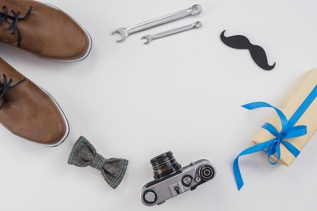 Frame van gereedschappen, camera en man schoenen op tafel Gratis Foto
