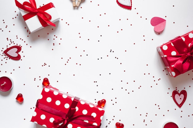 Frame van geschenken, confetti, kaarsen en harten op een witte achtergrond. de achtergrond van valentijnsdag Premium Foto