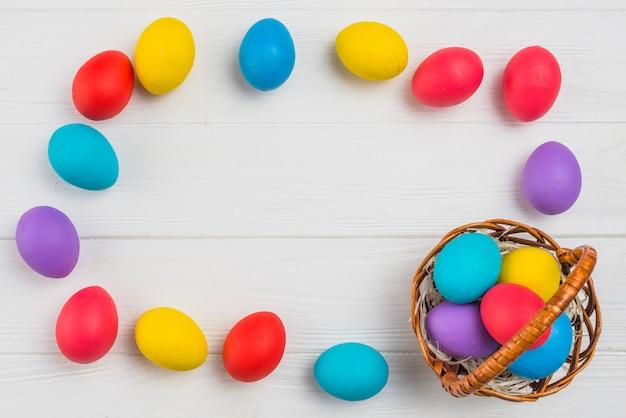 Frame van kleurrijke paaseieren en mand op tafel Gratis Foto