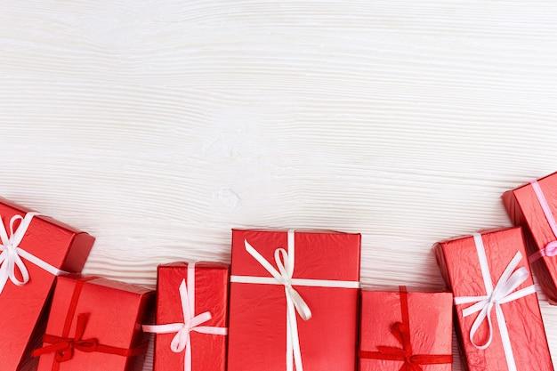 Frame van rode geschenken op wit hout Premium Foto