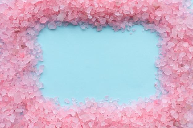 Frame van ruwe kristallen van roze zeezout op blauw Premium Foto