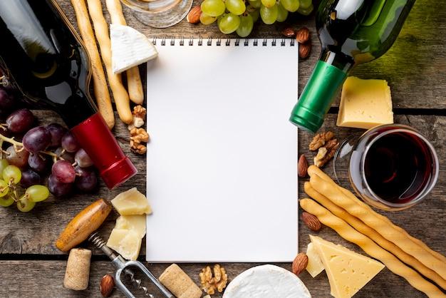 Frame van wijnflessen en snack naast notitieboekje Gratis Foto