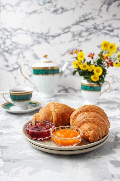 Frans ontbijt met croissants, abrikozenjam, kersenjam en een kopje thee, rode en gele bloemen Gratis Foto