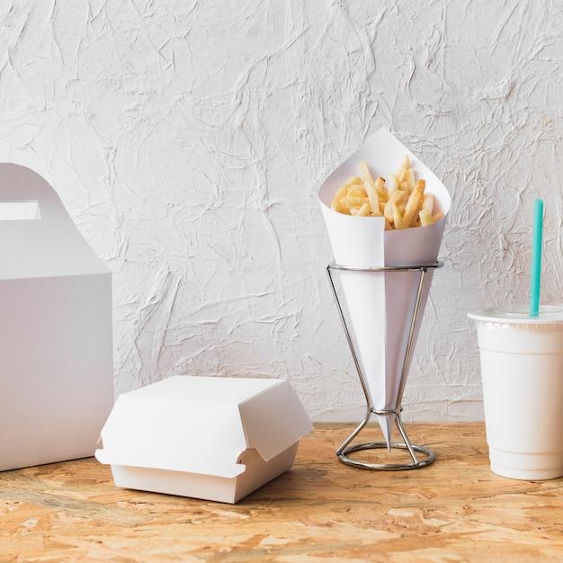 Franse frietjes; afzetbeker en voedselpakket op houten bureau Gratis Foto