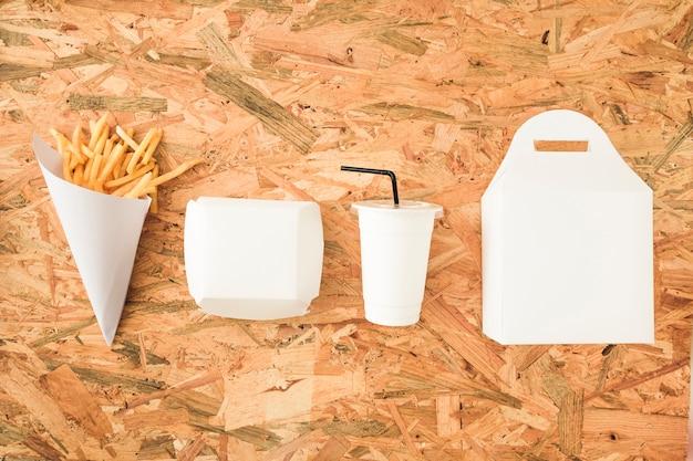 Franse frietjes; beker en verpakkingen op een rij op houten tafel Gratis Foto
