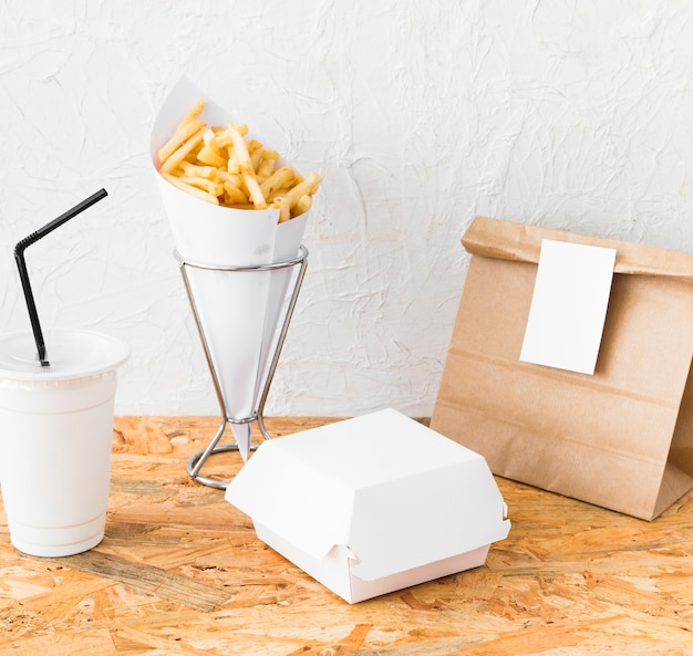 Franse frietjes; verwijdering beker; en voedselpakket op houten bureau Gratis Foto